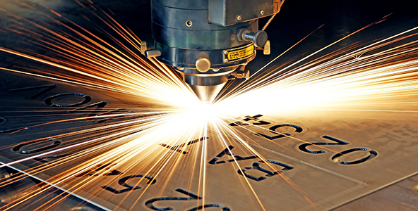 Stock image of computer laser cutting with sparks